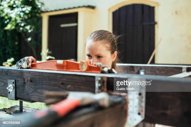 Woman building garden deck using a level.