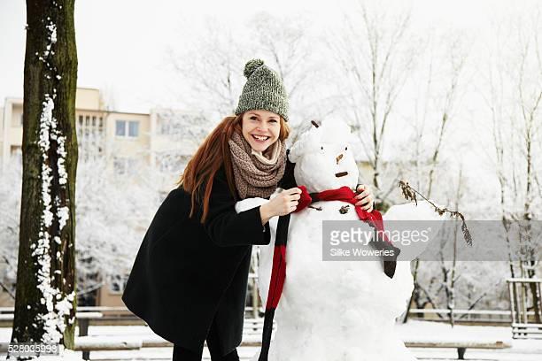 Woman building snowman