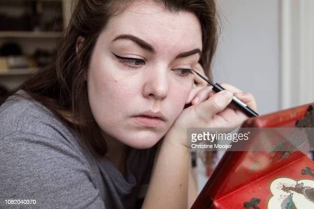 young adult putting on eyeliner - アイライナー ストックフォトと画像