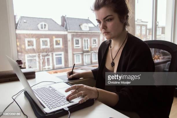 young adult woman working behind desk - benelux stockfoto's en -beelden