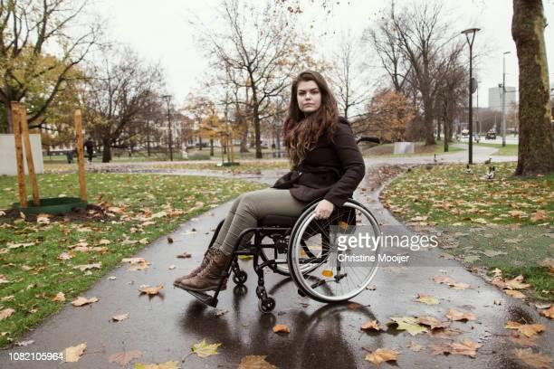 portrait of young adult woman in wheelchair - benelux stockfoto's en -beelden