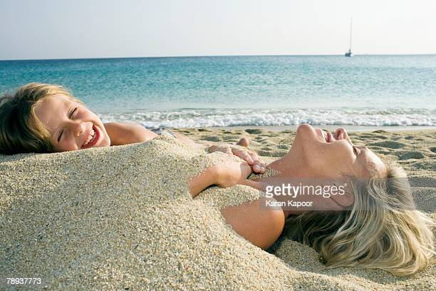 woman buried in sand at the beach with young girl leaning on her and laughing. - enterrar imagens e fotografias de stock