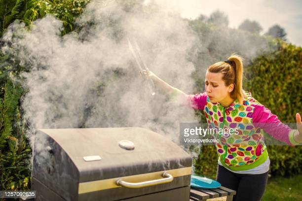 woman burning food on a barbecue in backyard - ember stock pictures, royalty-free photos & images