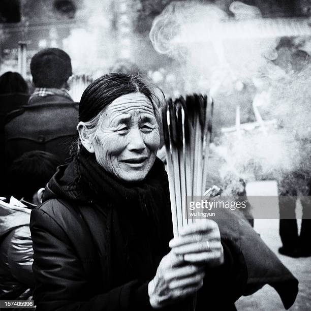 Woman burning incense and praying on the Chinese new year at Chenghuang Temple of Shanghai.
