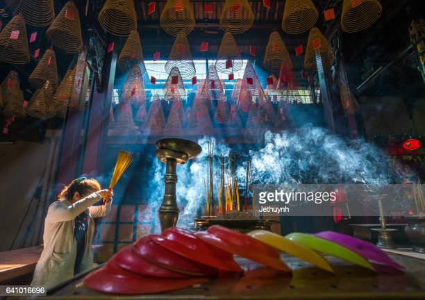 Woman Burning Incense to praying in Thien Hau Temple - Ho Chi Minh City
