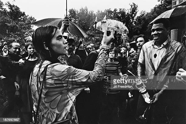 A woman burns a conscription draft card in the rain at a peace demonstration against the Vietnam War Washington DC 1968