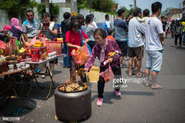 A woman burns fake paper money on day two of the nine day Mazu pilgrimage on April 14 2018 in Dadu Taiwan The annual Mazu Pilgrimage begins at Jenn...