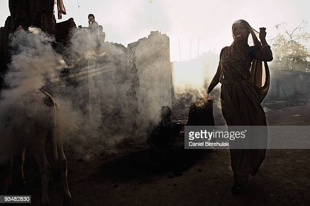 A woman burns fuel near the Union Carbide factory on November 29 2009 in Bhopal India Twentyfive years after an explosion causing a mass gas leak in...
