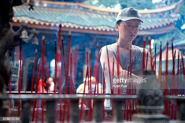 Woman burns incense at the Nanputuo Temple in Xiamen. The Nanputuo Temple is located on the southeast of Xiamen Island. It is surrounded by the...
