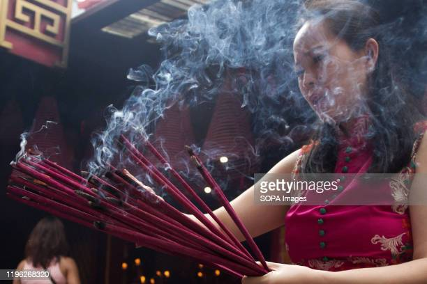 Woman burns incense while praying during the Chinese New Year celebration at a Temple in Jakarta.