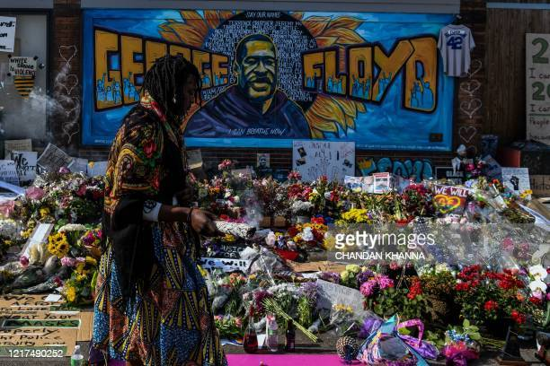 A woman burns sage and offers prayers as she pays her respects at a makeshift memorial in honour of George Floyd on June 3 2020 in Minneapolis...