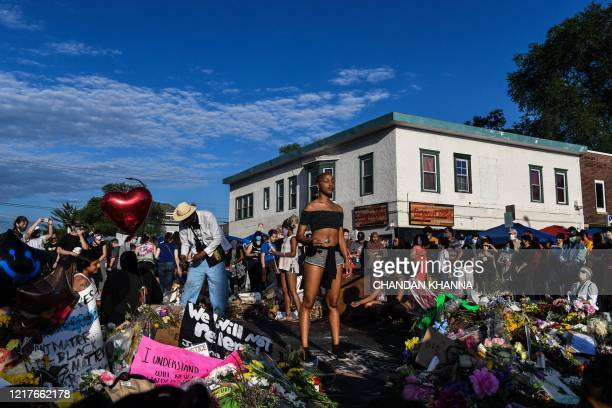 Woman burns sage and offers prayers as she pays her respects at a makeshift memorial in honour of George Floyd, on June 4, 2020 in Minneapolis,...