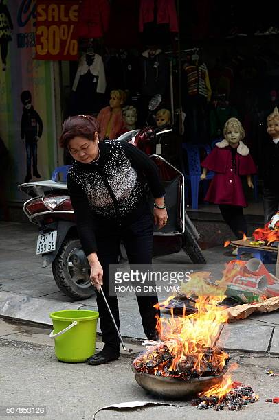 A woman burns votive papers including Kitchen Gods hats and shoes as an offering along a street in downtown Hanoi on February 1 2016 as Vietnamese...