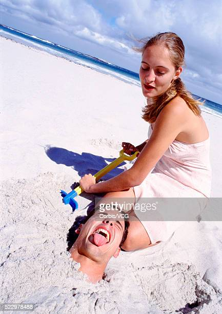 woman burying man in the sand - burying stock pictures, royalty-free photos & images