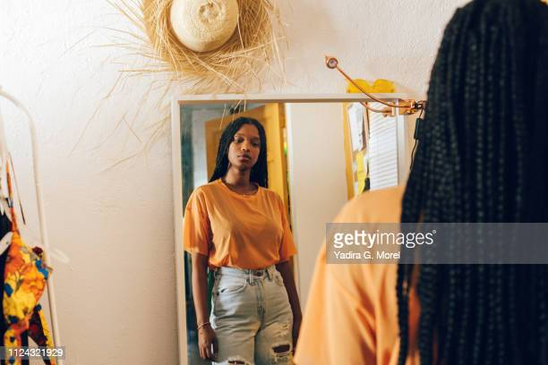 young woman looking in the mirror - femme antillaise photos et images de collection