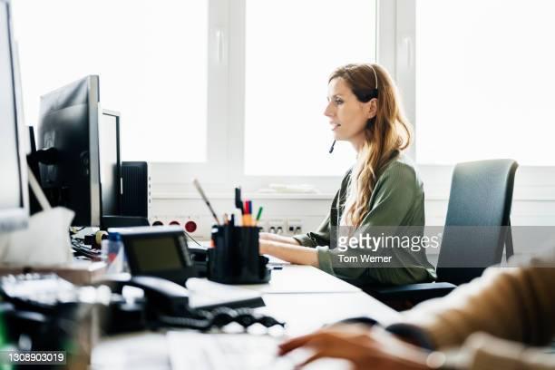 woman busy at work talking to customers on the phone - werkneemster stockfoto's en -beelden