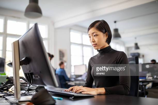 woman busy working at her desk in open plan office - japanese ethnicity stock pictures, royalty-free photos & images