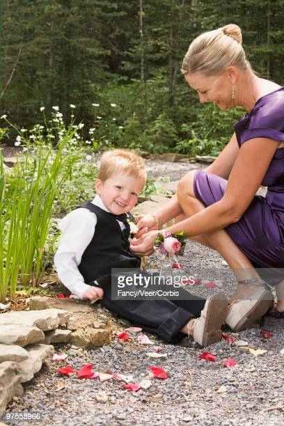 woman buttoning boy's vest - ring bearer stock pictures, royalty-free photos & images