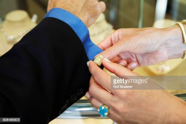 Woman buttoning husband's cuff link