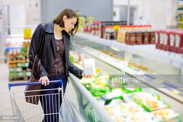 woman buy frozen fish in the supermarket