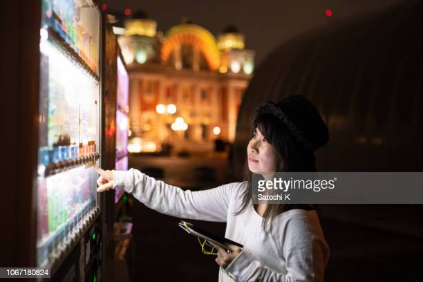 woman buying a bottle of drink in vending machine - vending machine stock photos and pictures