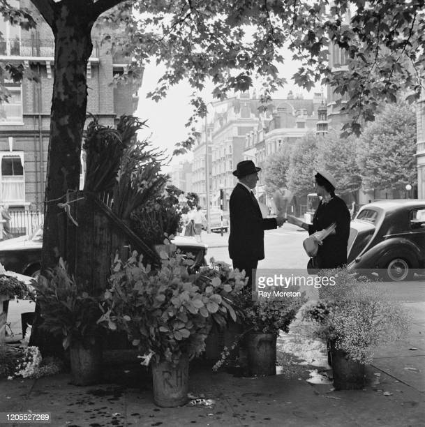 A woman buying a bouquet from a flower seller in Sloane Square Chelsea London September 1959