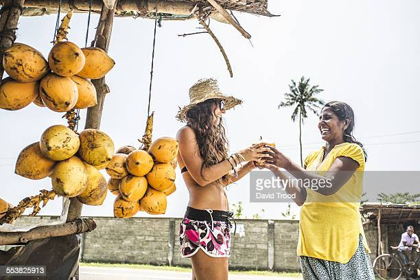 Woman buying a coconut at a roadside fruit shop.