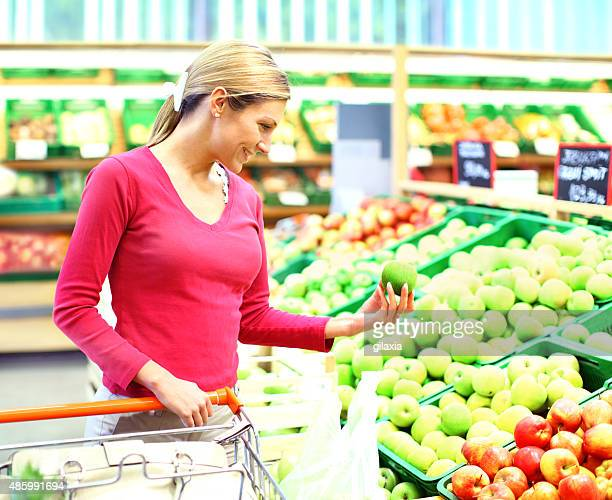 Woman buying apples in supermarket.