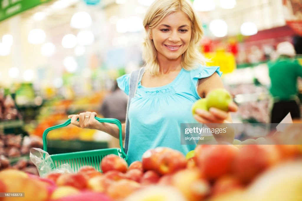 Woman buying apples in the fruit store. : Stock Photo