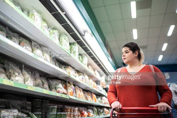 woman buying at supermarket - fat nutrient stock pictures, royalty-free photos & images