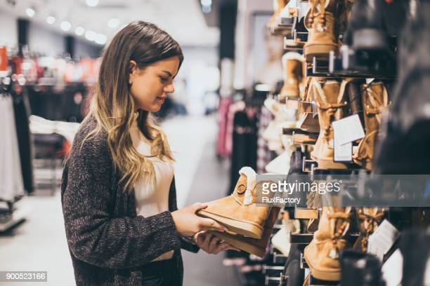 woman buying boots - brown shoe stock photos and pictures