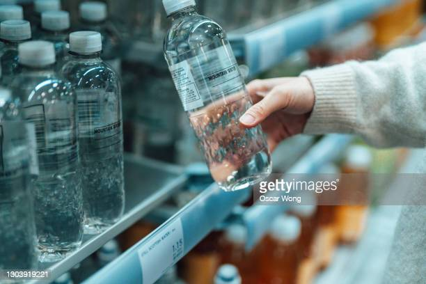 woman buying bottled water in convenience store - choice stock pictures, royalty-free photos & images