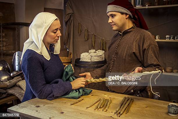 Woman buying candles in the apothecary of Diotaiuti Imola Italy mid14th century Historical reenactment