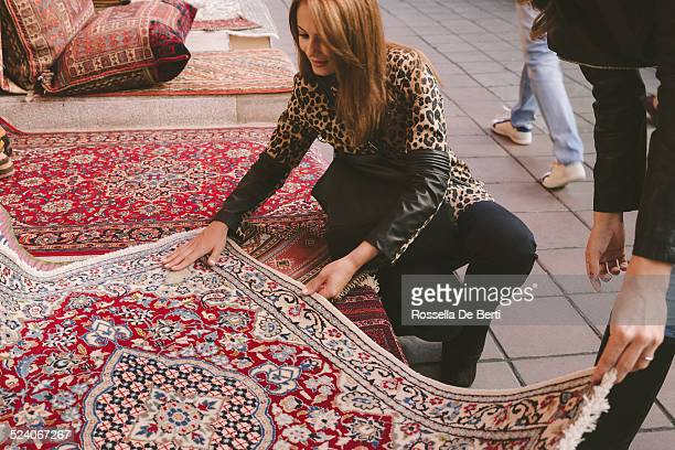 woman buying carpets - persian rug stock photos and pictures