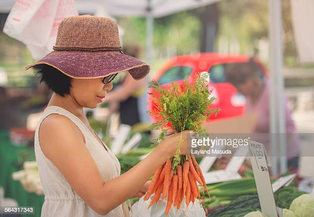 Woman Buying Carrots