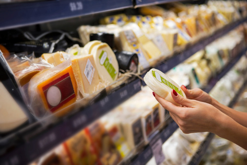 Woman buying cheese ina supermarket 488965867