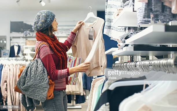 woman buying clothes at department store. - red shirt stock pictures, royalty-free photos & images