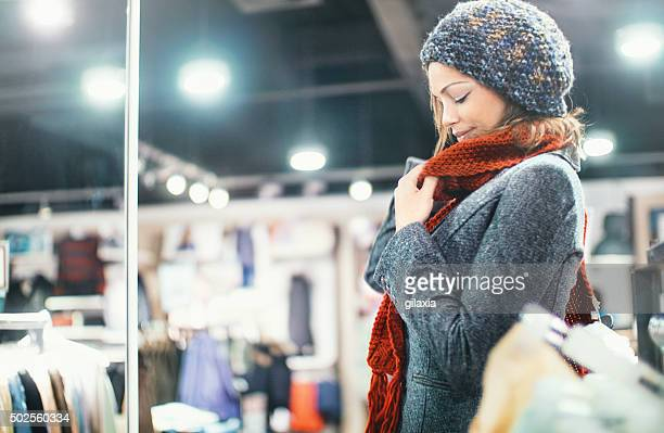 Woman buying clothes at department store.