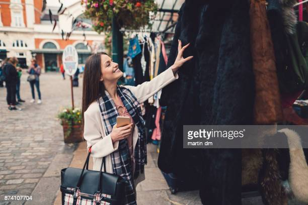 woman buying clothes at the street market - fashion collection stock pictures, royalty-free photos & images