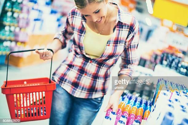 Mujer de compras en el supermercado los productos cosméticos.