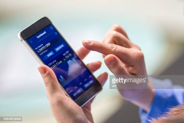 woman buying cryptocurrency through mobile phone app - mobile app stock pictures, royalty-free photos & images