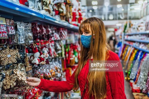 mujer comprando decoraciones para árbol de navidad - henri coste fotografías e imágenes de stock