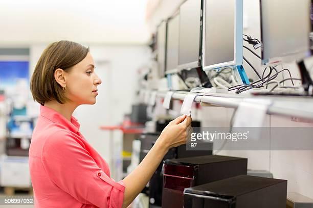 woman buying desktop in store