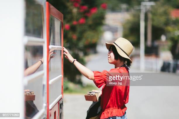 woman buying drink from vending machine - vending machine stock photos and pictures