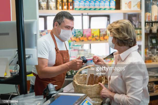 woman buying essentials at the grocery store during the quarantine and wearing a facemask - biosecurity stock pictures, royalty-free photos & images