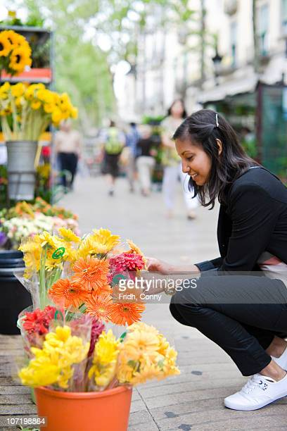 Woman buying flowers at market stall