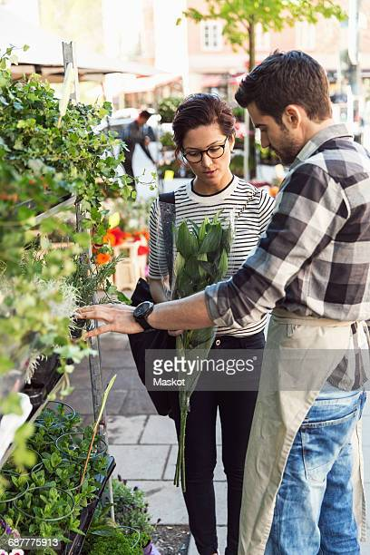 Woman buying flowers from male owner on sidewalk