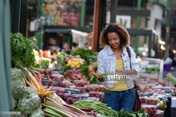 woman buying food at an organic market - food and drink stock pictures, royalty-free photos & images