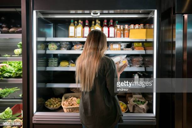 woman buying food at the supermarket - organic stock pictures, royalty-free photos & images