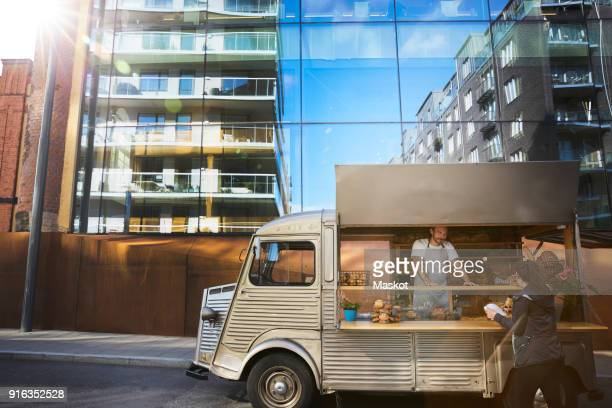woman buying food from male owner at food truck on city street - mid adult stock pictures, royalty-free photos & images